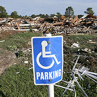 Piles of debris stand behind the handicap parking sign as crews from Century Construction continue to tear down the President's gate apartment complex on Lawndale Thursday.