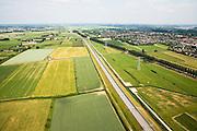 Nederland, Gelderland, Knooppunt Ressen, 28-06-2006; luchtfoto (25 procent  toeslag foto gemaakt vanaf knooppunt Ressen, pal Oost richting Bemmel: de Betuweroute (midden) loopt vanaf Rotterdam parallel aan de A15; maar na het knooppunt Ressen (tussen Nijmegen en Arnhem) vlak voor Bemmel, gaat de A15 over in tweebaansweg, rechts met bomen, om na circa 2 kilometer geheel te stoppen stopt; op termijn zal de A15 vermoedelijk doorgetrokken worden, richting Duitsland;.Betuwelijn, landschap, milieu, transport, verkeer en vervoer, vrachtvervoer, logistiek, infrastructuur, mobiliteit, landschap, planologie; .zie ook andere foto's van deze lokatie (lucht en panorama deel van de serie Panorama Nederland.luchtfoto (toeslag aerial photo (additional fee required .foto Siebe Swart / photo Siebe Swart