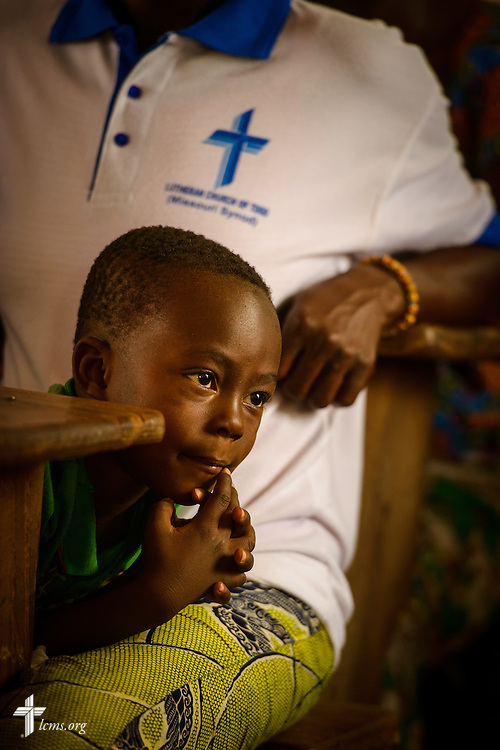 A young boy lies in his mother's lap following a Bible study at the Lutheran Church of Togo in Lokpano on Monday, Feb. 13, 2017, in Lokpano, Togo. LCMS Communications/Erik M. Lunsford