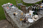 The aftermath debris of glasses, bottles, cans and plates, the morning after a 50th birthday party, spread around the garden in the Herefordshire countryside, on 23rd June 2019, in Kington, Herefordshire, England.