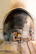 MARRAKESH, MOROCCO - November 16 2017 - Workers bake bread at a communal oven in the Mellah. Communal ovens - or 'ferranes' - are collectively shared by communities and are found at the heart of Medinas all across Morocco. Locals pay a small sum to bake bread and other foods like roast chickens and sardines in the large fire oven, which also bake breads and pastries in bulk to be sold around the Medina. The ovens are often connected to and heat the water for the local hammams (public baths) at the same time.  Mellah, Marrakesh Medina, Morocco