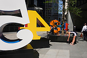 A city worker smokes a cigarette as a woman stretches hamstrings after exercise next to an art installation entitled 'One Through Zero (The Ten Numbers)' by American pop artist Robert Indiana (b 1928), in Lime Street, City of London, the capital's Square Mile, and its financial heart. Situated in the capital's Square Mile, its financial heart, are surrounding offices and corporate headquarters from the finance and insurance sector, most notably being the nearby Lloyds of London building. This series of sculptures is composed of 10 brightly painted numerical digits, each made of aluminum and set on its own base. Their construction took place at the former Lippincott Foundry in North Haven, Connecticut from 1980 to 1983