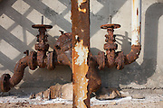 The shadows of rusting industrial pipes and gate valves on a abandoned factory site now on wasteland in Northfleet Thames Gateway