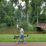 Nederland Rotterdam Deelgemeente prins alexander 06-06-2008 20080606 Foto: David Rozing ..Lageland, groene deelgemeente, vrouw laat hond uit .Deelgemeente Prins Alexander is het op 1 na diepst / laag gelegen gebied in Nederland, het laagste punt in de deelgemeent is  6,67 meter beneden NAP, in lageland. Prins Alexander, second deepest area in the Netherlands, deepest point in this area, below sealevel: - 6,67m NAP..Foto: David Rozing