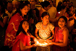 Children worshipping by candlelight in celebration of Navratri; the Hindu festival of Nine Nights,