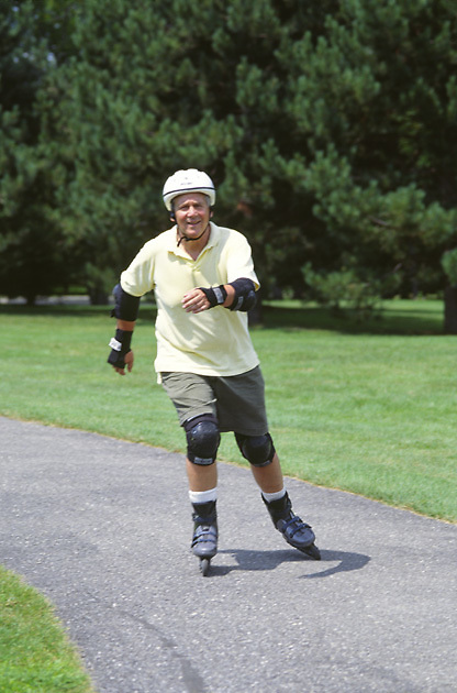 senior man rollerblading, using protective gear