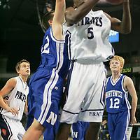 Forward Arvel Long (5) fights for a basket against a host of Lion defenders.