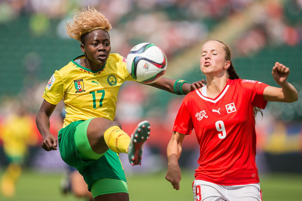 Cameroon's Gaelle Enganamouit  kicks the ball from Swiss defender Lia Waelti ball during the first half of their FIFA Women's World Cup group C match at Commonwealth Stadium in Edmonton, Canada on June 16, 2015.   AFP PHOTO/GEOFF ROBINS