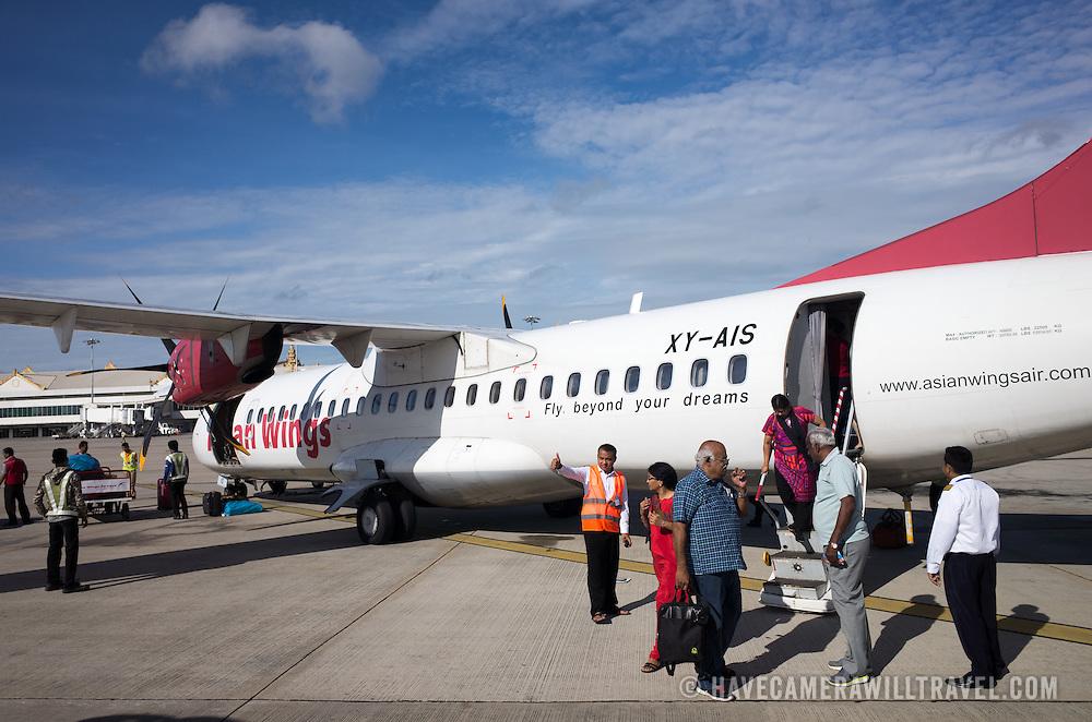 An Asian Wings plane unloads its passengers on the tarmac of Mandalay Airport, Myanmar (Burma).