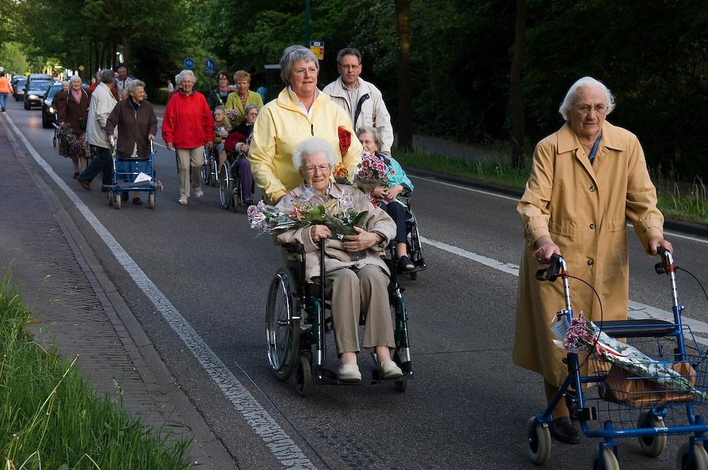 Nederland, Driebergen, 18 mei 2006..Avond-Rollator-4-daagse in Driebergen eindigt met defile..Verzorgingshuis Beukenstein heeft dit jaar een avondvierdaagse georganiseerd voor de ouderen met wieltjes. In rolstoel of met rollator wandelden 4 avonden achter elkaar zo'n 100 bejaarden. Vandaag was de laatste avond, die traditioneel afgesloten werd met een vrolijk defile. Zelfs de Hoofdstraat, de doorgaande weg door Driebergen, werd even voor alle verkeer afgesloten zodat de sportievelingen in volle glorie, en voorafgegaan door de fanfare, het terrein van het verzorgingshuis konden oplopen... . Foto (c) Michiel Wijnbergh..residents of an old peoples home finish their 4-days walk