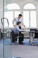 Two business men using laptop in office