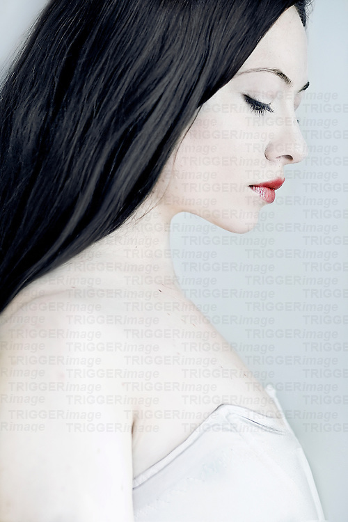 A close up of a girl with black hair and pale skin.