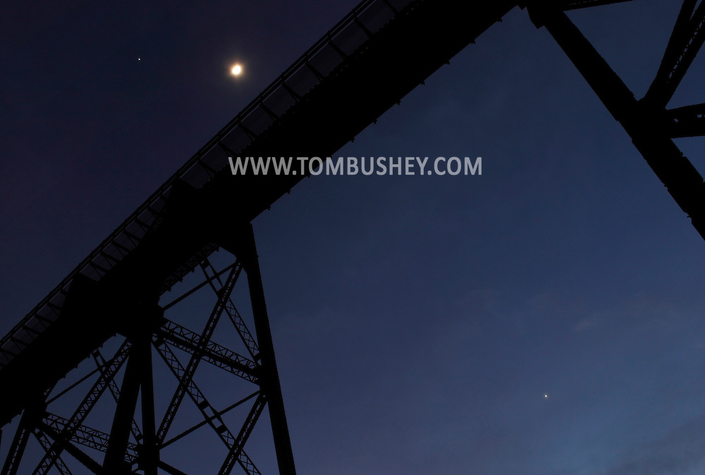 Cornwall, New York - The planet Jupiter, top left, the moon and the planet Venus, lower right, share the twilight sky above the Moodna Viaduct railroad trestle on Jan. 29, 2012.