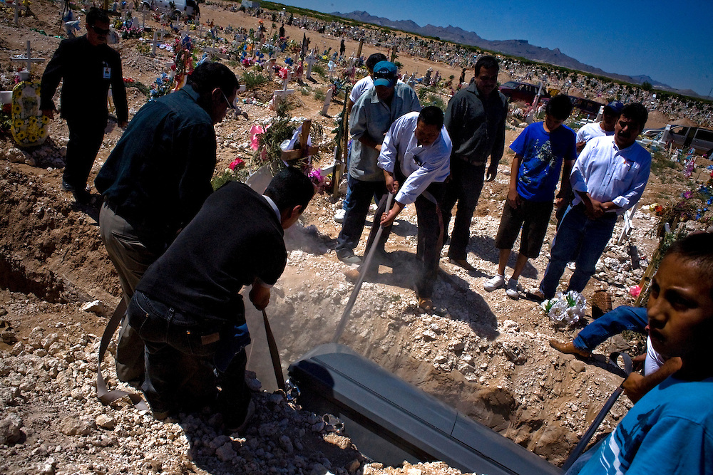Family members look on as grave workers lower the body of a Municipal Police officer in Ciudad Juarez, Chihuahua on May 21, 2010. The victim was 41-year-old municipal police officer, he was shot outside his home.