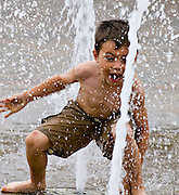 Boy enjoying first signs of summer at the water fountain.