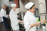 Three chefs work side by side in busy kitchen