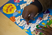 A school-grade 2 African kid plays a board game designed to improve children's literacy called 'Cloudy Sky' in Zonnebloem School, Cape Town, South Africa.  The game has been provided to the school by Shine Centre which is a charity that aims to address the high illiteracy rate in South Africa by improving literacy levels among children in schools and disadvantaged communities.