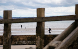 Portobello, Edinburgh. Scotland, UK. 11 April, 2020. On Easter weekend Saturday morning the public were outdoors exercising and walking on Portobello beach outside of Edinburgh. The popular beach and promenade was very quiet and people were exercising proper social distancing.  Iain Masterton/Alamy Live News