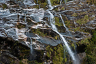 Water cascades over gneiss rock formations and mossy growth in the Clinton Canyon, Milford Track, Fiordland, New Zealand, Fiordland, New Zealand, Fiordland, New Zealand