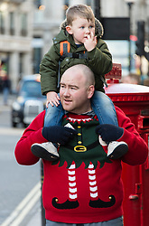 © Licensed to London News Pictures. 20/12/2014. London, UK. A father wearing an elf Christmas jumper carries his young son on his shoulders as they shop on London's Regent Street on the last saturday before. Photo credit : Richard Isaac/LNP