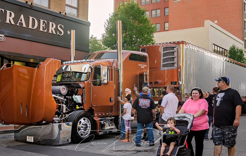"""Truck enthusiasts inspect """"Redneck Low,"""" Sweet Rides Logistics' 2005 Kenworth T600 and 2017 Wabash Trailer after the 34th annual Shell Rotella SuperRigs parade, June 10, 2016, in Joplin, Missouri. SuperRigs, organized by Shell Oil Company, is an annual beauty contest for working trucks. Approximately 89 trucks entered this year's competition. (Photo by Carmen K. Sisson/Cloudybright)"""
