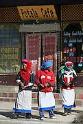 Tibetan women chat outside a popular restaurant called the Potala Cafe on a street corner in Shangri-La.
