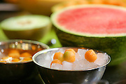 Fruit salad, scooping balls of sweet melon into a bowl of ice. This image has a restriction for licensing in Israel