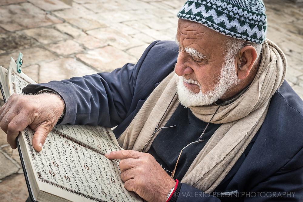 A man at Al Aqsa mosque learns to read using a copy of the Quran.
