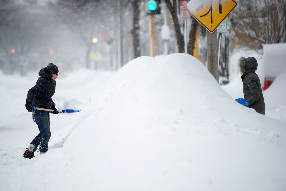 """(20130209, Somerville, Massachusetts)-..Liz Stein (left) and Jessica Grimsby (right) shovel snow in between buried cars during Winter Storm Nemo in Somerville, Massachusetts on Saturday, Feb. 9, 2013.  """"I was in the Blizzard of 1978 and this is just as bad,"""" said Stein...Photo by Brooks Canaday/The Weather Channel"""