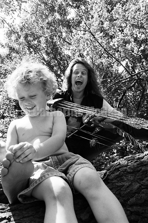 NEW YORK - JUNE 1993:  American rock musicianTed Nugent, holding bows and arrows, laughs while his son Rocco grabs his toe in Central Park in June 1993 in New York City, New York.  (Photo by Catherine McGann).Copyright 2010 Catherine McGann