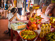 """26 AUGUST 2013 - BANGKOK, THAILAND:     Women pray before donating food staples to the Poh Teck Tung Foundation for Hungry Ghost Month in Bangkok. Poh Teck Tung operates hospitals and schools and provides assistance to the poor in Thailand. The seventh lunar month (August - September in 2013) is when the Chinese community believes that hell's gate will open to allow spirits to roam freely in the human world for a month. Many households and temples will hold prayer ceremonies throughout the month-long Hungry Ghost Festival (Phor Thor) to appease the spirits. During the festival, believers will also worship the Tai Su Yeah (King of Hades) in the form of paper effigies which will be """"sent back"""" to hell after the effigies are burnt.   PHOTO BY JACK KURTZ"""