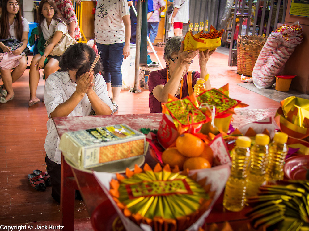 "26 AUGUST 2013 - BANGKOK, THAILAND:     Women pray before donating food staples to the Poh Teck Tung Foundation for Hungry Ghost Month in Bangkok. Poh Teck Tung operates hospitals and schools and provides assistance to the poor in Thailand. The seventh lunar month (August - September in 2013) is when the Chinese community believes that hell's gate will open to allow spirits to roam freely in the human world for a month. Many households and temples will hold prayer ceremonies throughout the month-long Hungry Ghost Festival (Phor Thor) to appease the spirits. During the festival, believers will also worship the Tai Su Yeah (King of Hades) in the form of paper effigies which will be ""sent back"" to hell after the effigies are burnt.   PHOTO BY JACK KURTZ"