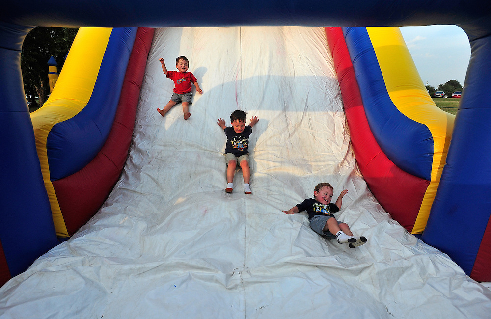 Isaiah Johnson, 3, from left, Seth Lanard,5, and Silas Lanard laugh as the go down an inflatable slide during a free community farewell concert at the Navy Supply Corps School on Friday, Sept. 17, 2010 in Athens, Ga. .