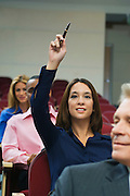 Business people sitting in auditorium, woman rising hand
