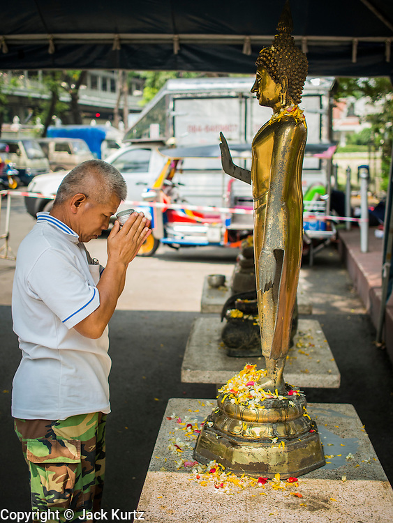 "10 APRIL 2014 - BANGKOK, THAILAND:  A man prays at a Buddha statue at Wat Pathumwanaram Ratchaworawiharn in central Bangkok put out for Songkran. Songkran, also called the ""Water Festival"" is the traditional Thai New Year. It was celebrated as the New Year until 1940, when Thailand made January 1 the official start of the New Year. Songkran is now a three day holiday starting on April 13. Many people go to temples to make merit in the days leading up to Songkran. They bathe Buddha statues to bring themselves good luck in the coming year. The holiday is best known for water fights and throwing water at strangers. Thais and foreigners go out with giant squirt guns or buckets of water and throw the water at strangers.   PHOTO BY JACK KURTZ"