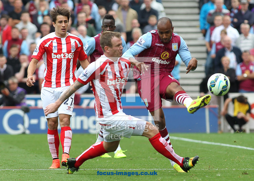 Glenn Whelan of Stoke City and Fabian Delph of Aston Villa in action during the Barclays Premier League match at the Britannia Stadium, Stoke-on-Trent.<br /> Picture by Michael Sedgwick/Focus Images Ltd +44 7900 363072<br /> 16/08/2014