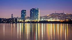 Foto noturna do skyline da capital gaúcha com reflexo no rio Guaíba e vista para o BarraShopping Sul, no bairro Cristal. Ao fundo, o morro Santa Teresa e a torre de transmissão da RBS TV.   FOTO: Gustavo Roth / Agência Preview