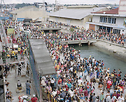 Thousands of passengers and families gather at the Port of Ambon waiting for KM Tidar. The passengers were heading to their hometown during 2015 Christmas holiday located in various places such Banda Islands, Kei Islands, Aru Islands, and Papua.<br /> <br /> Indonesia&rsquo;s Pelni is the last great true passenger liners company in the world. It is the only company of its size that still serves scheduled vessels transporting people across various destination. In a far-flung archipelago nation, where many of the islands have no airport and most of its area made up of water, it is one important mean of transportation&mdash;and simply one of the best way to travel. One of Pelni's furthest regular route starts from Surabaya in East Java and ends in Papuan city of Merauke, basically the eastern end of Indonesia. The round trip voyage takes one month, passing more than two dozen ports and covering a distance of more than 8,000 kilometers.