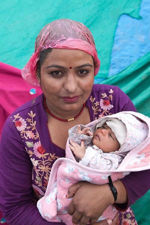 Baby van 9 dagen oud, geboren een paar dagen voor de eerste aardbeving, in de armen van haar moeder, in een tentenkamp in Kathmandu.