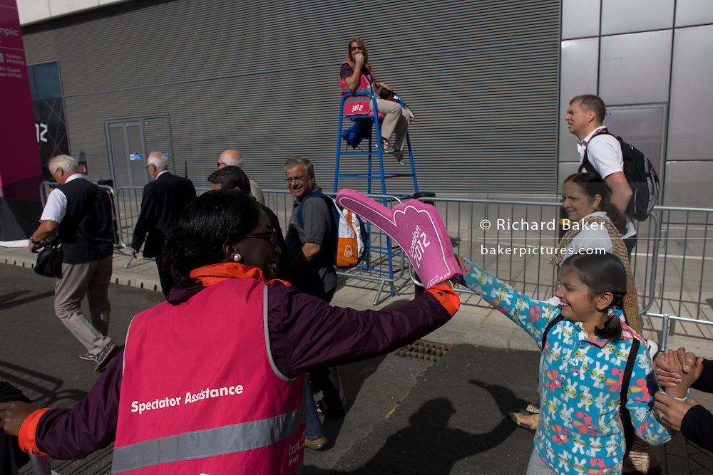 A Games Maker volunteer offers a high-five to a young spectator arriving with her family for the London 2012 Olympics. Situated on the fringe of the Olympic park, Westfield is Europe's largest urban shopping centre. This land was transformed to become a 2.5 Sq Km sporting complex, once industrial businesses and now the venue of eight venues including the main arena, Aquatics Centre and Velodrome plus the athletes' Olympic Village. After the Olympics, the park is to be known as Queen Elizabeth Olympic Park.