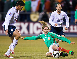 Mexico midfielder Leandro Augusto (6) slides for the ball in front of United States forward Brian Ching (11) and United States midfielder Landon Donovan (10).  The United States men's soccer team defeated the Mexican national team 2-0 in CONCACAF final group qualifying for the 2010 World Cup at Columbus Crew Stadium in Columbus, Ohio on February 11, 2009.