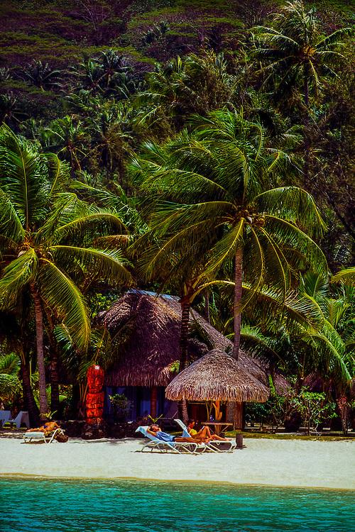 Couple lounging on beach, Bora Bora, French Polynesia