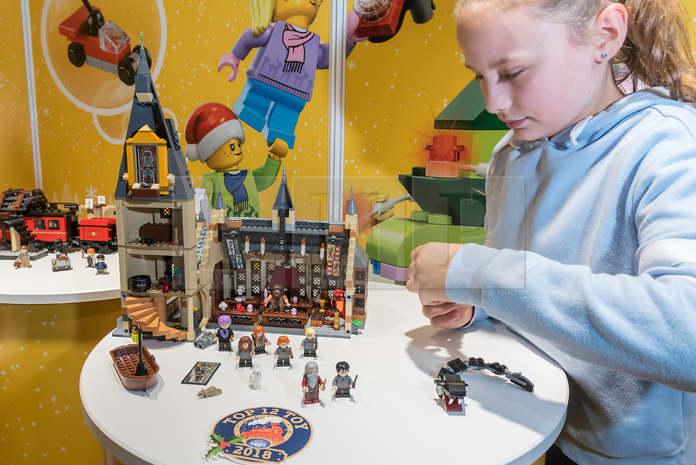 """© Licensed to London News Pictures. 14/11/2018. LONDON, UK. Isabella, aged 10, plays with Harry Potter Hogwarts Great Hall by LEGO.  Preview of """"DreamToys"""", the official toys and games Christmas Preview, held at St Mary's church in Marylebone.  Recognised as the countdown to Christmas, the Toy Retailer's Association, an independent panel of leading UK toy retailers, have selected the definitive and most authoritative list of what toys will be the hottest property this Christmas. [Child models provided by show organisers, permission obtained to be photographed].  Photo credit: Stephen Chung/LNP"""