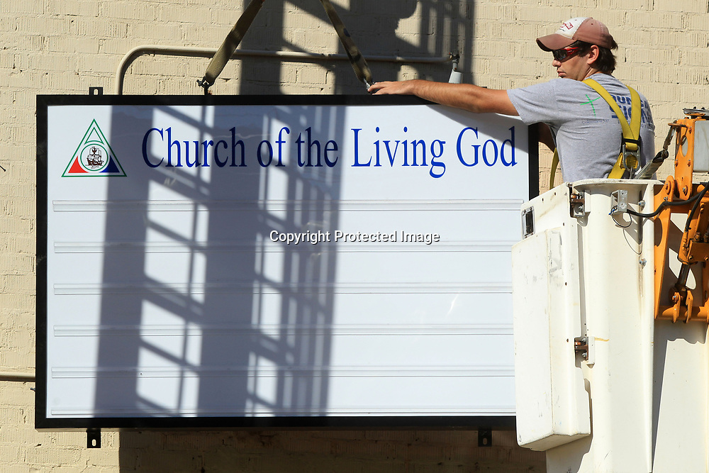 Josh Easley, of Tupelo and a employee at Duncan Signs, levels up a new LED box sign being installed at The Church of the Living God Wednesday morning in Tupelo.