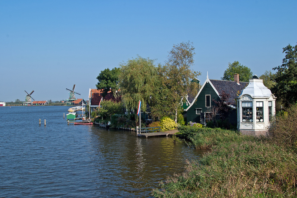 "A waterside look at the approach to Zaanse Schans, known for its historial authenticity and antique windmills.  This is a popular day trip for Amsterdam visitors.  .From Wikipedia: "" Zaanse Schans is a neighbourhood of Zaandam, near Zaandijk in the municipality of Zaanstad in the Netherlands, in the province of North Holland. It has a collection of well-preserved historic windmills and houses; the ca. 35 houses from all over the Zaanstreek were moved to the museum area in the 1970s. The Zaans Museum, established in 1994, is located in the Zaanse Schans..The Zaanse Schans is one of the popular tourist attractions of the region and an anchor point of ERIH, the European Route of Industrial Heritage. The neighbourhood attracts approximately 900,000 visitors every year..The windmills were built after 1574."".Also from Wikipedia: "" Along the river Zaan, you can find still dozens of original windmills (mostly entirely made of wood), still technically functioning, some of them over 350 years old. Next to these there are many 19th century stone industrial buildings, nowadays derelict or converted into apartments, but still recognisable as industrial buildings.""."