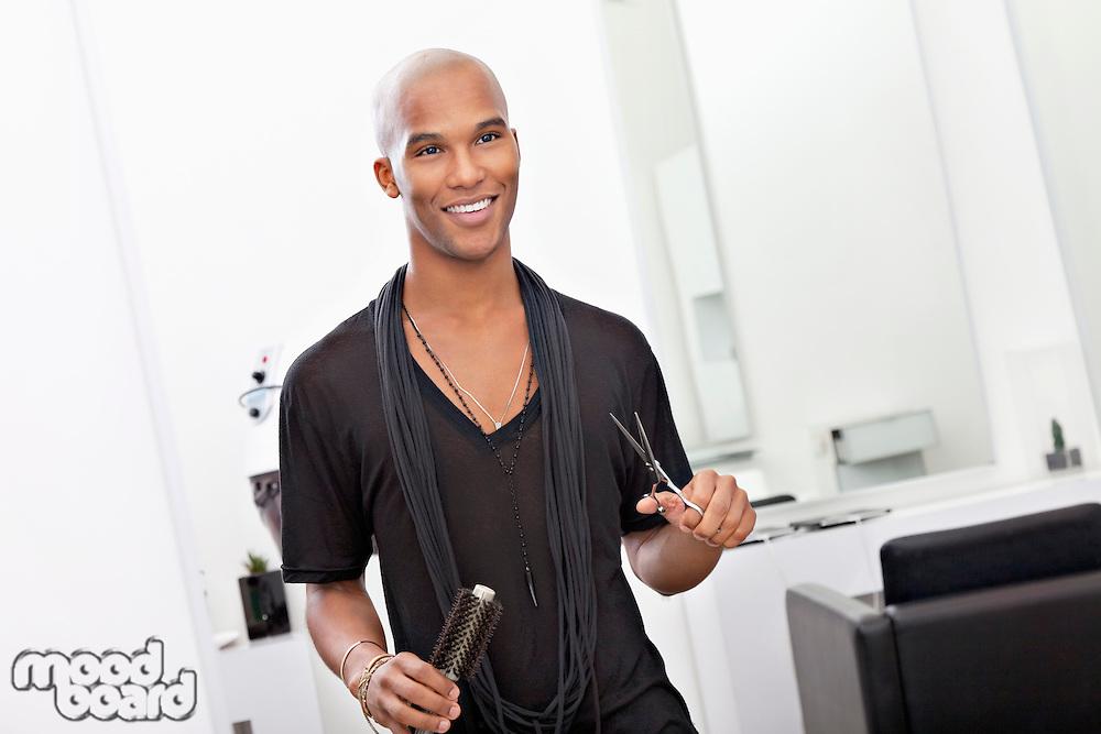 Smiling male hairdresser holding scissor and hairbrush