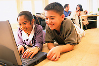 Brother and Sister Using Laptop --- Image by © Jim Cummins/CORBIS