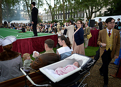 © Licensed to London News Pictures. 07/07/2012. London, UK  A baby sleeps amongst guests at 'The Chap's Olympiad' in central London on July 7th, 2012. 'The Chap' is a light-hearted magazine, aimed at revisiting the fashions and pastimes of the polite aspects of 1920's to 1950's England. The annual Olympiad event sees competitors take part in events such the 'Cucumber Sandwich Discus', 'The Umbrella Joust' and 'The Tug of Hair'e. Photo credit : Stephen Simpson/LNP