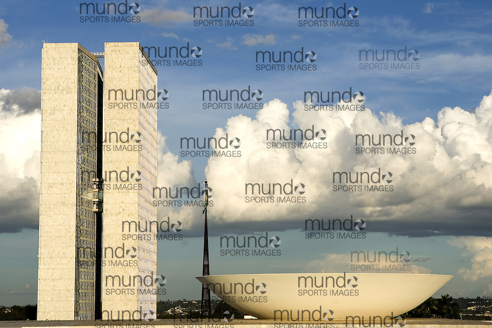 Detail of The Brazilian National Congress building at the end of the Esplanada dos Ministerios (Esplanade of the Ministries) in Brasília. The tower is office space for members of national congress, the tea cup-like structure is the national chamber of deputies meeting room, and the flag pole in the background is a monument set up during the military regime. The building was designed by Oscar Neimeyer.