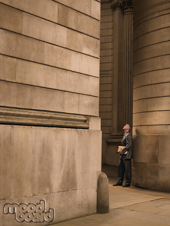 Businessman standing in entrance to monumental building looking up